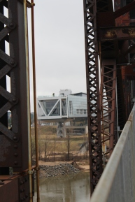 A peek through the girders of the foot bridge at Clinton's Library.