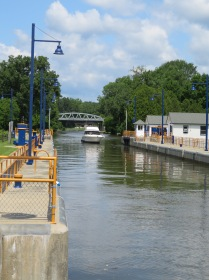 The boat approaches the lock with the gates open for it.