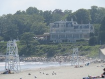 "Looking down the beach at a restaurant called ""The Chanler at Cliff Walk"". The Cliff Walk begins there."